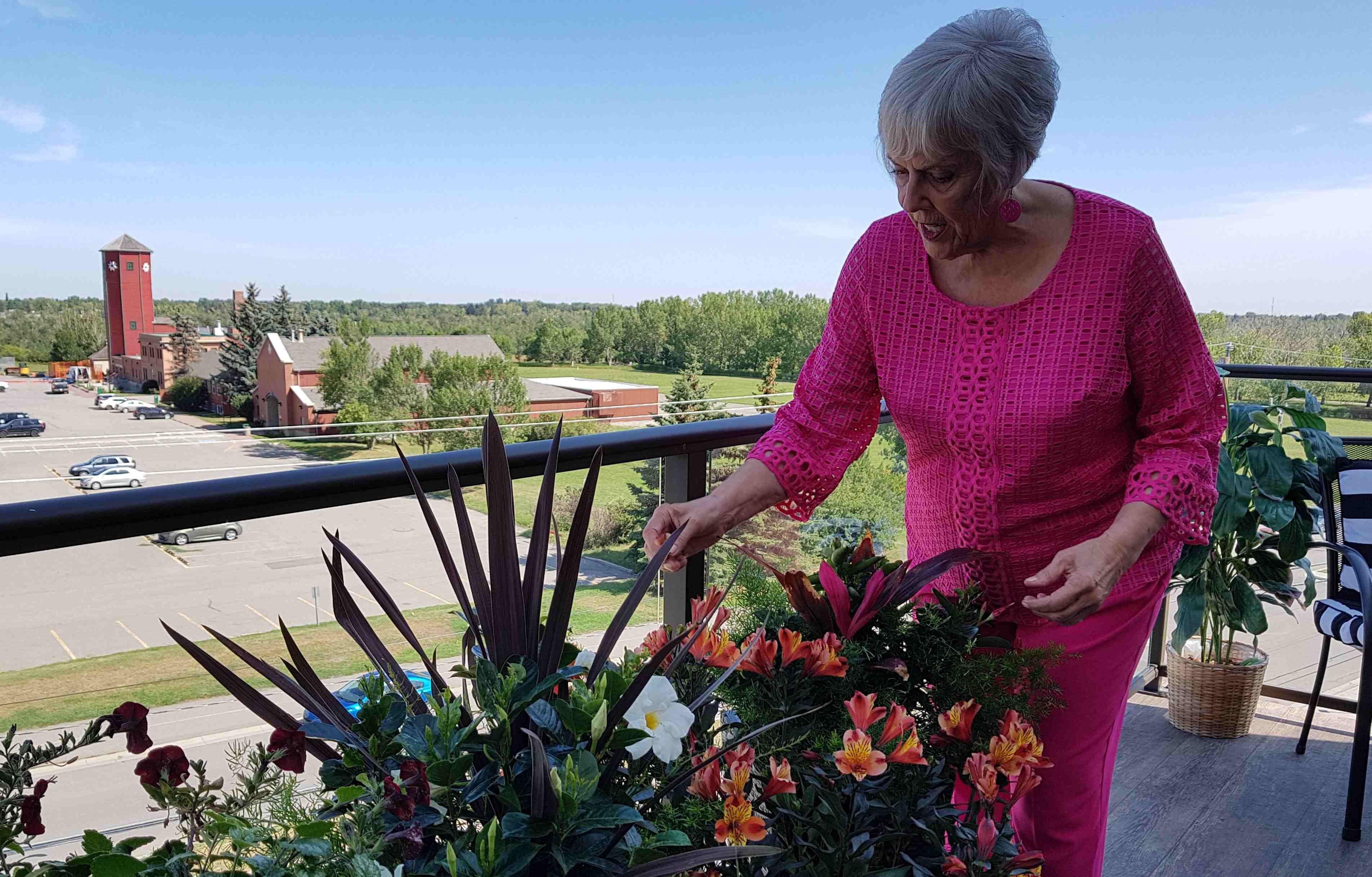 Diane tends garden on her deck overlooking Fish Creek Park