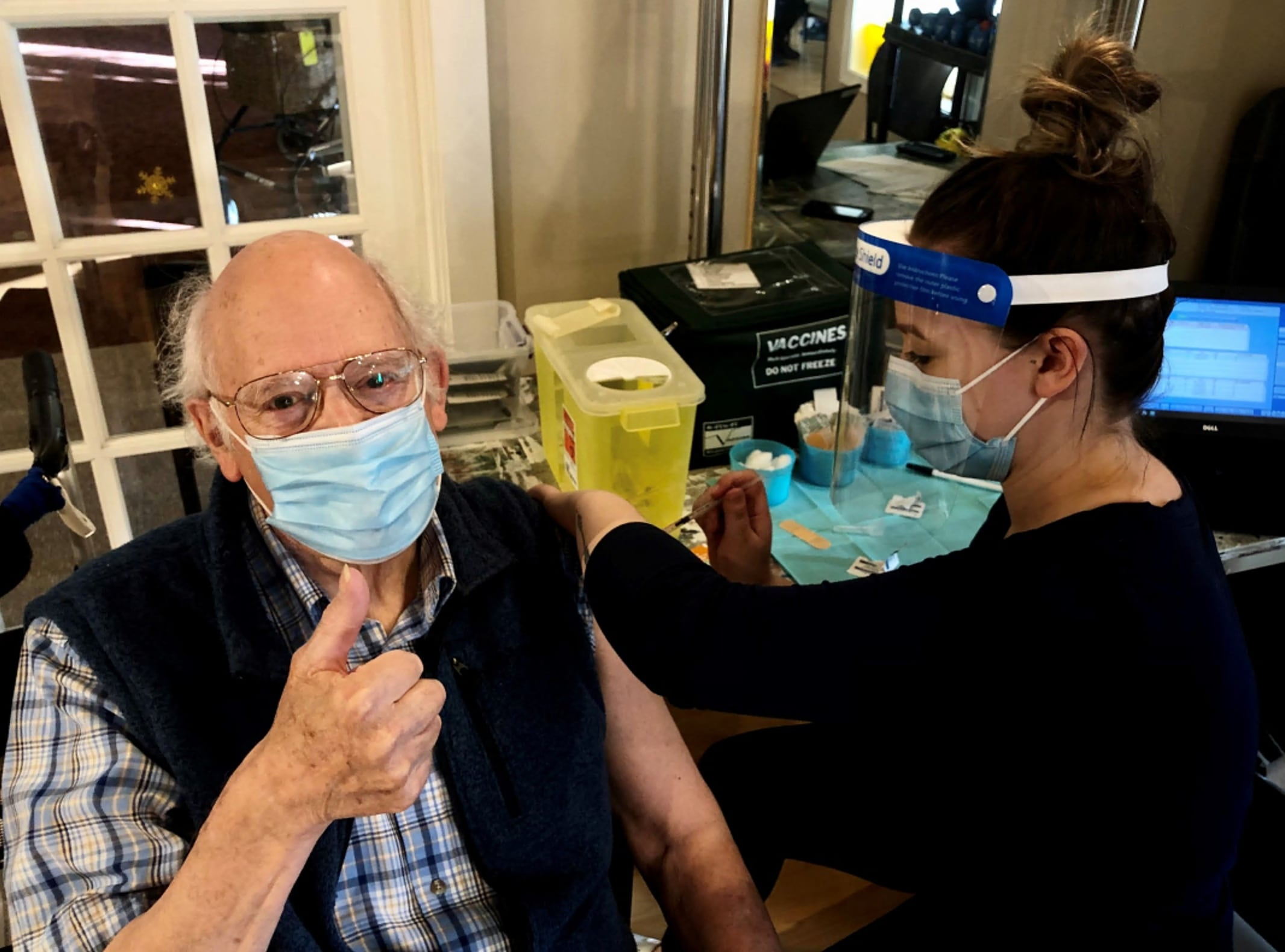 Garrison Green resident Jim Dolph gets his shot from an Alberta Health Services nurse