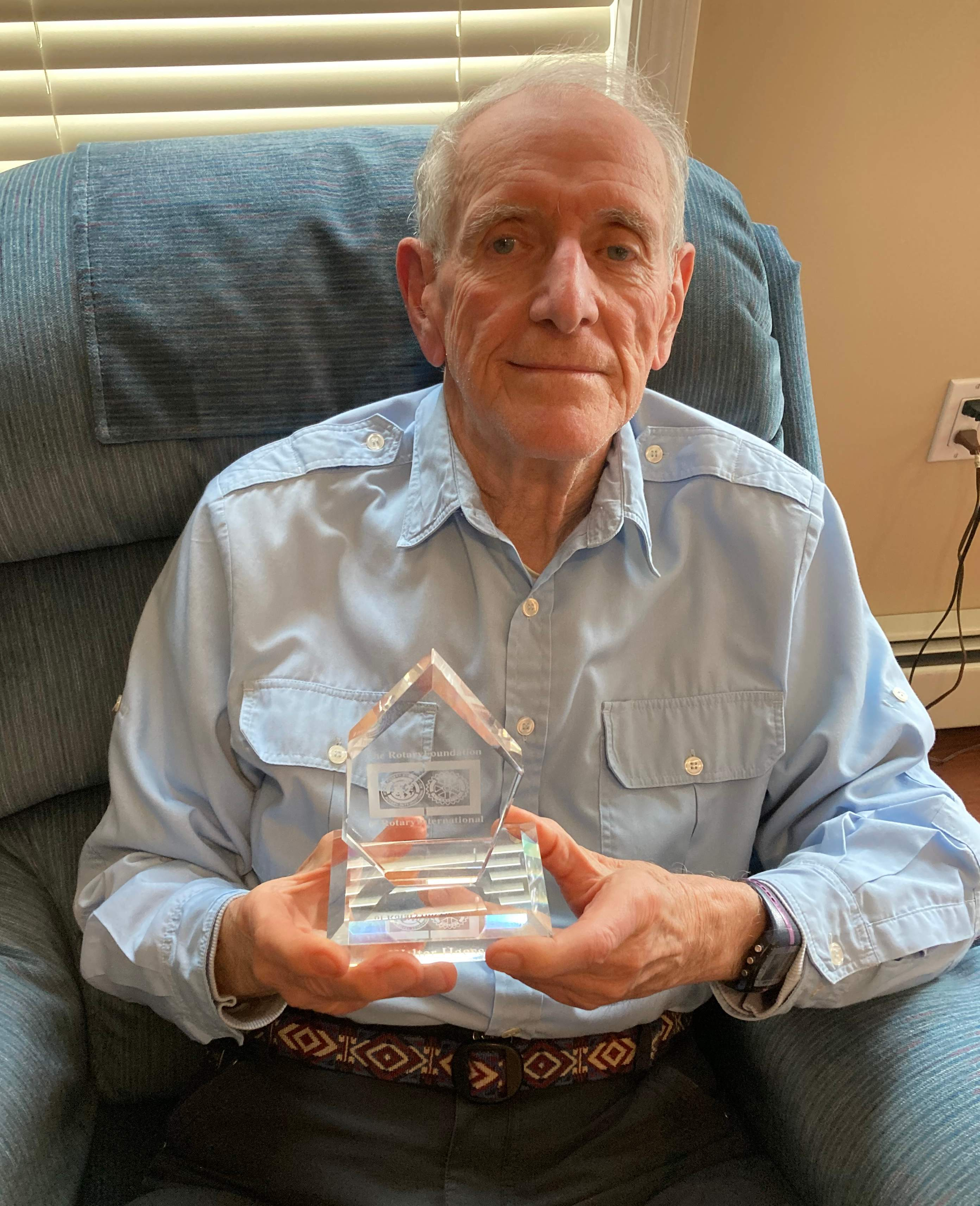 Long time Rotarian Walter Haessel holds one of several awards for his volunteer work